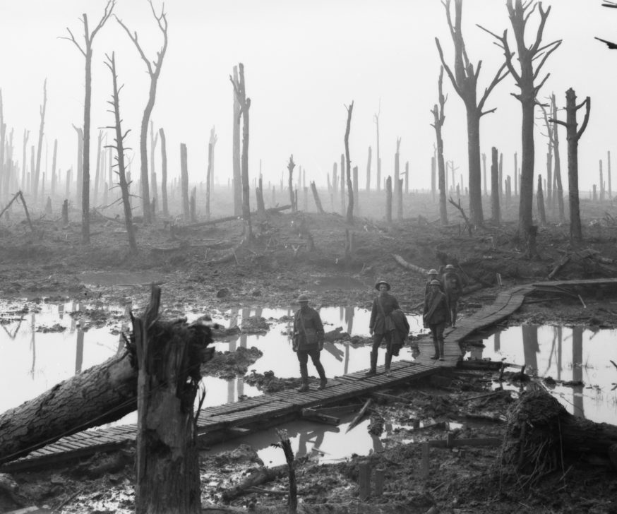 Australian soldiers crossing a duckboard, surrounded by water and a shelled landcscape