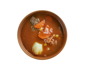 A bowl of stew showing meat, carrot and turnip