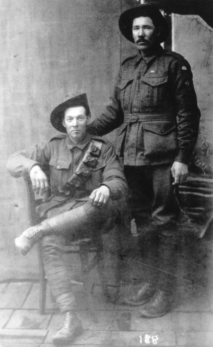 A studio portrait of two soldiers, one seated and the other standing, both in uniform