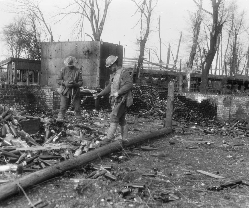 E00420 - Australian soldiers in Parcardie, Somme, looking at wine bottles left behind by German troops