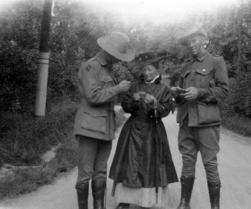 J00716--1- Soldiers showing photographs to a woman in England RESIZED